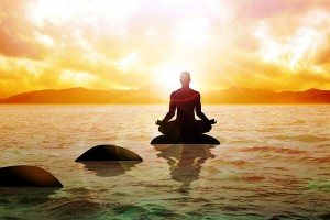 A man figure meditating on calm water during sunrise